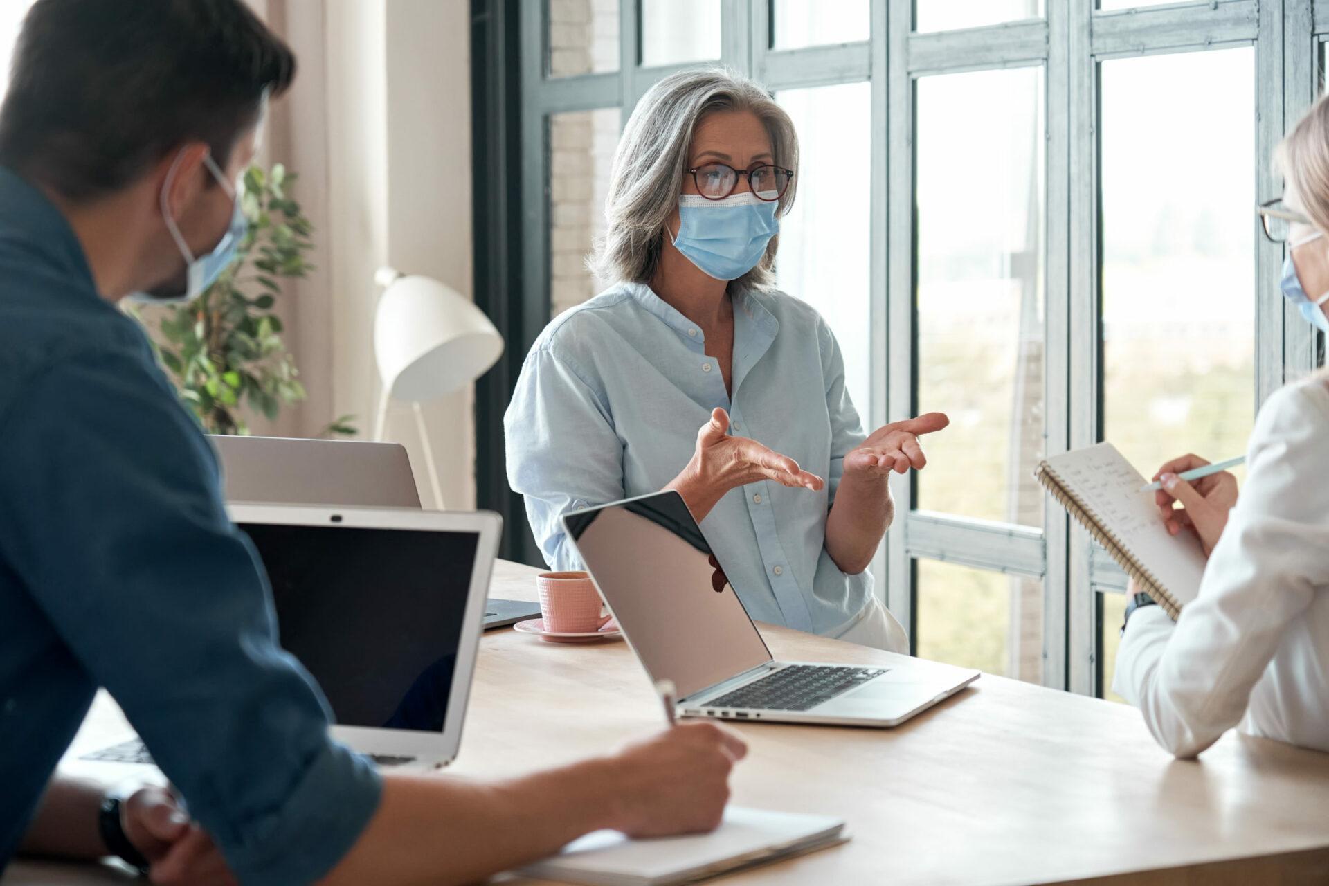 Agents immobiliers conseillant une femme propriétaire avec les gestes barrières